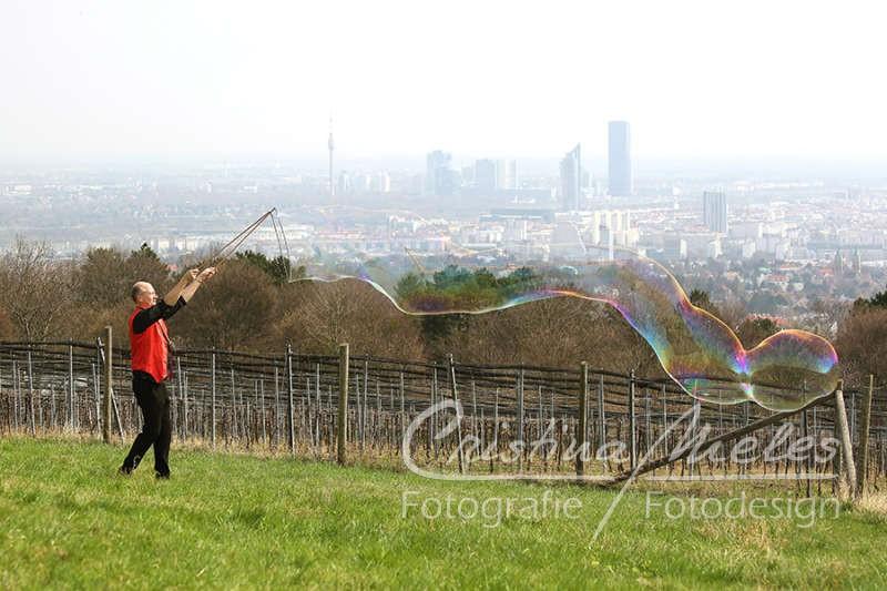 Zauberer zaubert eine lange Seifenblase vor der Wiener Kulisse