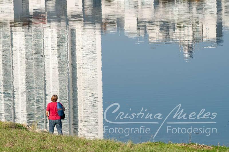Eine Dame bewundert die Spiegelung im Wasser an der Neuen Donau