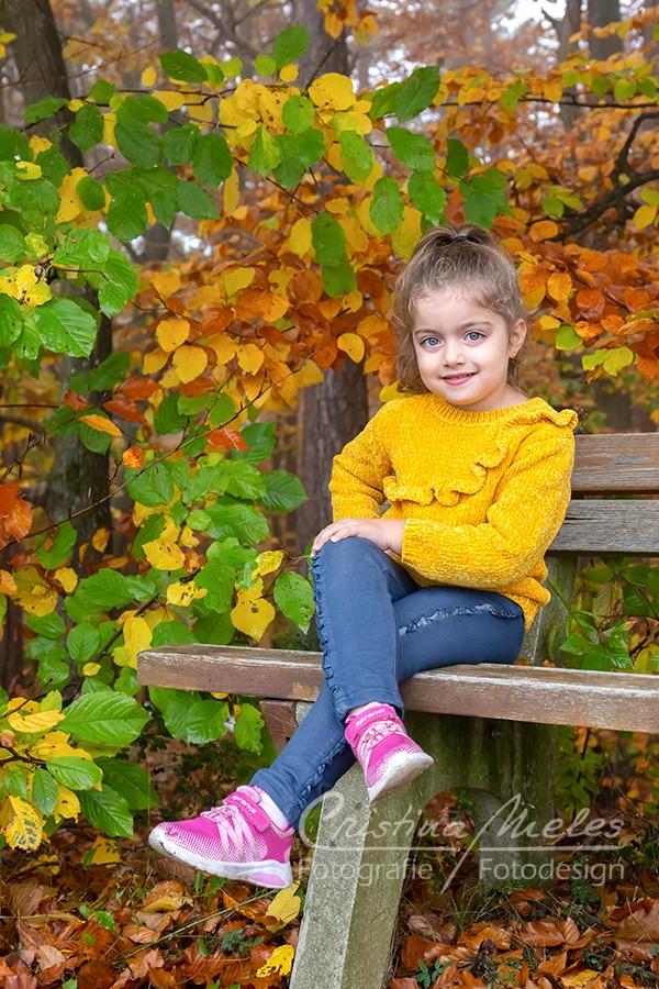 Fröhliches Mädchen auf einer Holzbank am Waldrand