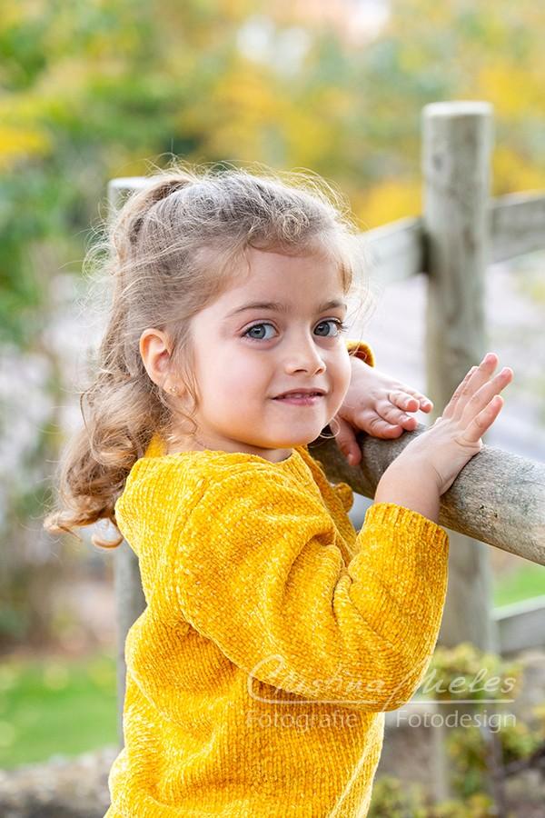 Kleines Mädchen mit langen lockigen Haaren und großen Augen