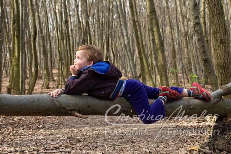 Kleines Kind chillt auf einem abgefallenen Baumstamm