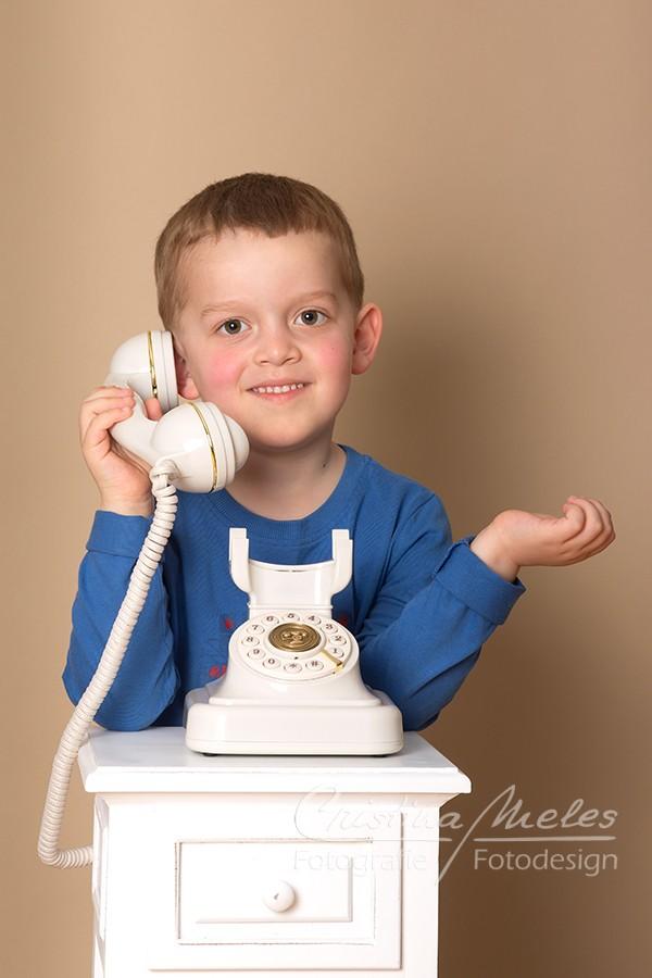 Junge telefoniert an einem alten Telefon - Fotos Meles